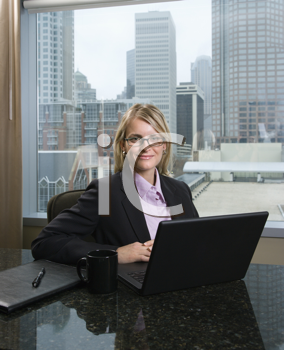 Caucasian businesswoman smiles at the camera while sitting at her laptop. The city can be seen through the window in the background. Vertical shot.