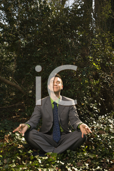 Young businessman sits in a lotus position meditating in the woods with closed eyes and a smile. Vertical shot.