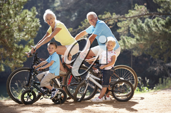 Senior couple with grandchildren on country bike ride