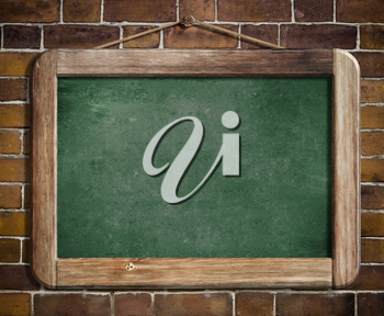 Aged green blackboard hanging on brick wall as a background for your message