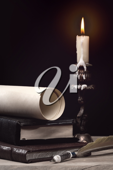 Royalty Free Photo of a Candle, Books, a Pen and Paper