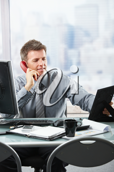 Happy businessman having conversation on landline phone looking at family photo smiling.