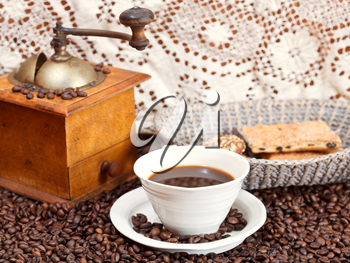 mug of coffee and roasted coffee beans with retro wooden manual mill, biscuit, openwork napkin