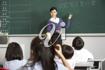 Teacher Standing By Blackboard In Chinese School Classroom