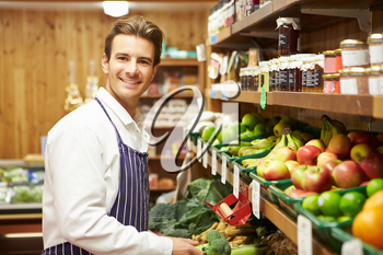 Male Sales Assistant At Vegetable Counter Of Farm Shop