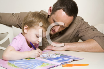 Royalty Free Photo of a Father Helping His Daughter With an Activity Book