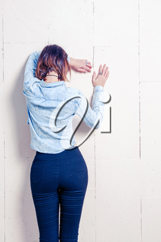 Rear view of a young woman in trendy wear leaning on painted wall with space for text, copy space