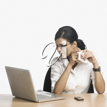 Businesswoman working on a laptop and drinking coffee