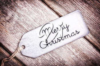 Metal tag with string, wishing a Merry Christmas, over old wood surface. Retro style processing.