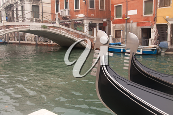 Two gondola in Venice near pier and bridge