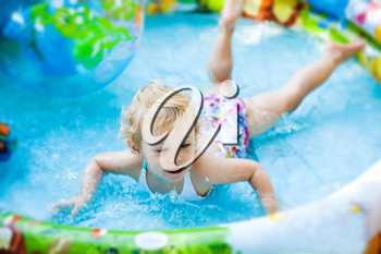 Little blondie girl in the swimming pool, soft focus
