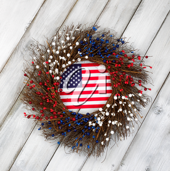 Wreath decorated for Independence Day with USA flag inside on rustic white wooden boards.