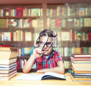 Scientist little child learns homework in the school library. Pupil in glasses against book shelves