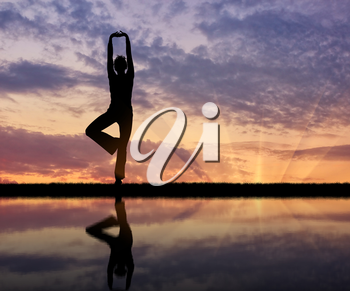 Concept of meditation and relaxation. Silhouette of a girl practicing yoga at sunset and reflection in water